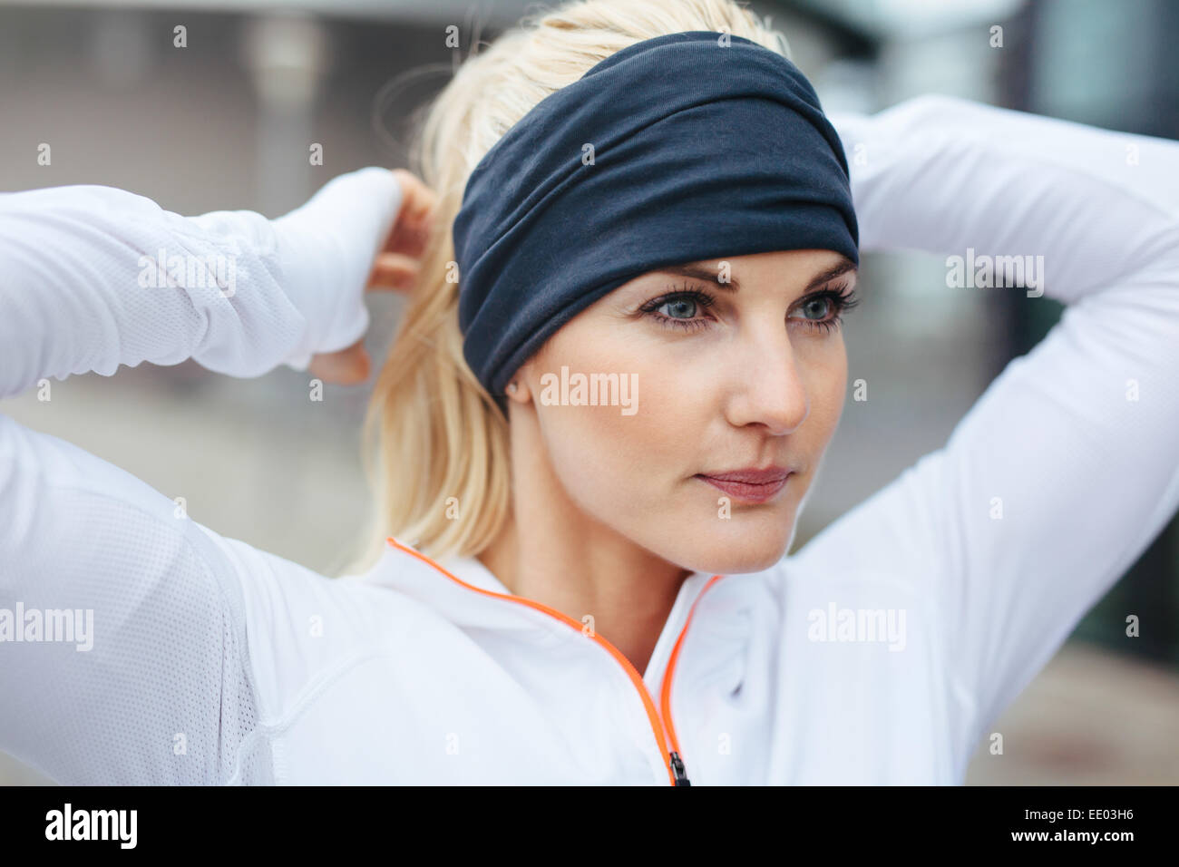 Close-up of young female athlete tying up hair  before a run. Sporty fitness woman on outdoor workout looking motivated. - Stock Image