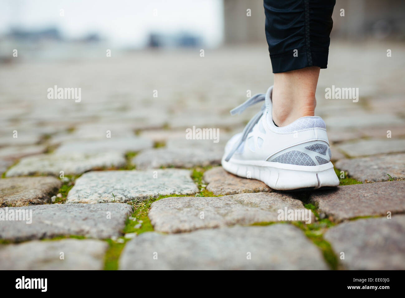 Leg of female jogger walking on pavement. Focus of shoes. Woman feet on sidewalk. - Stock Image