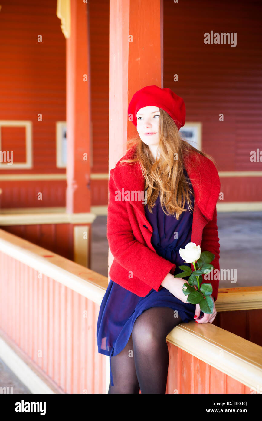 Woman on local station boundaries waiting upcoming train - Stock Image