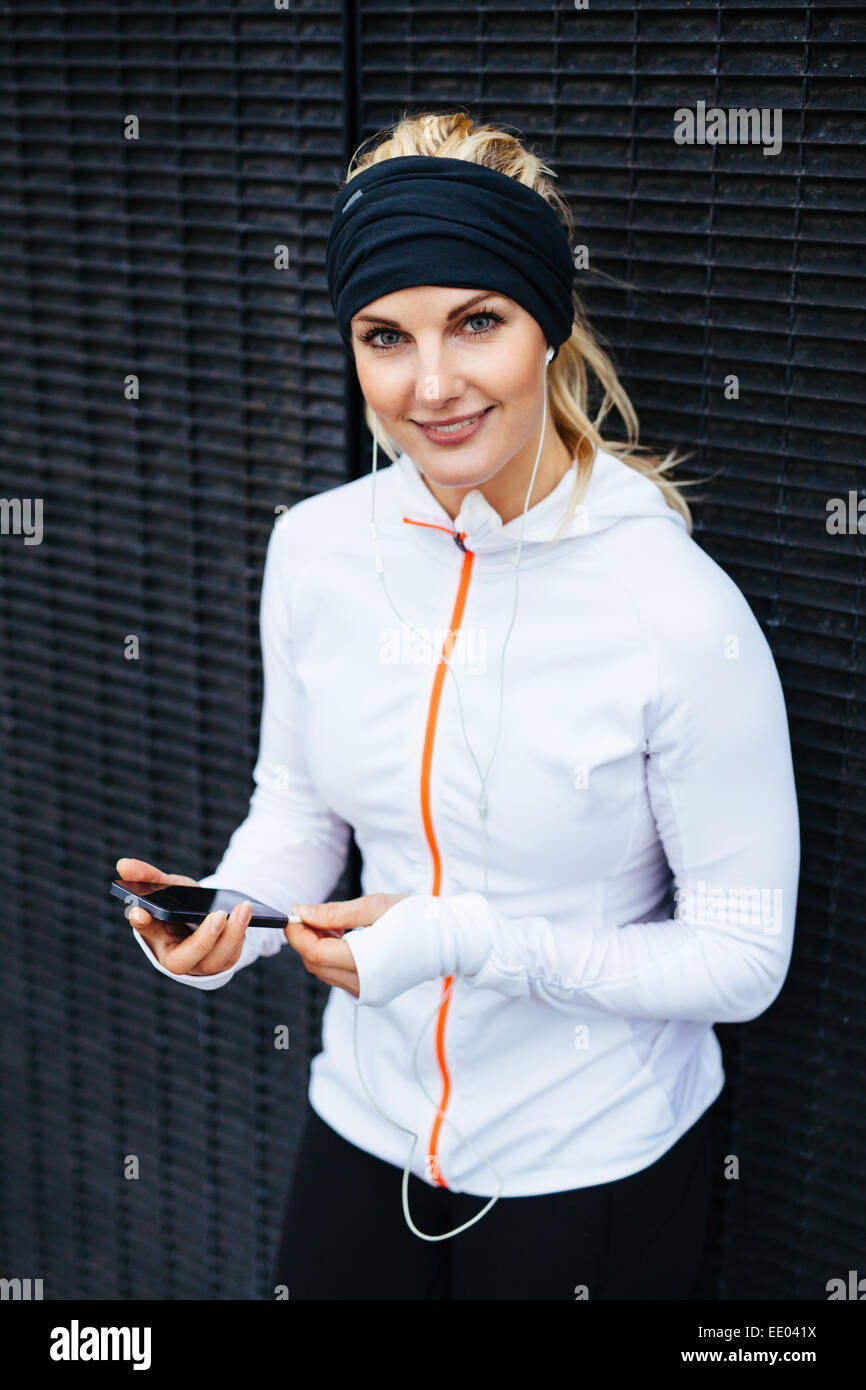 Portrait of attractive young woman listening to music on mobile phone. Female runner relaxing after a training session. - Stock Image
