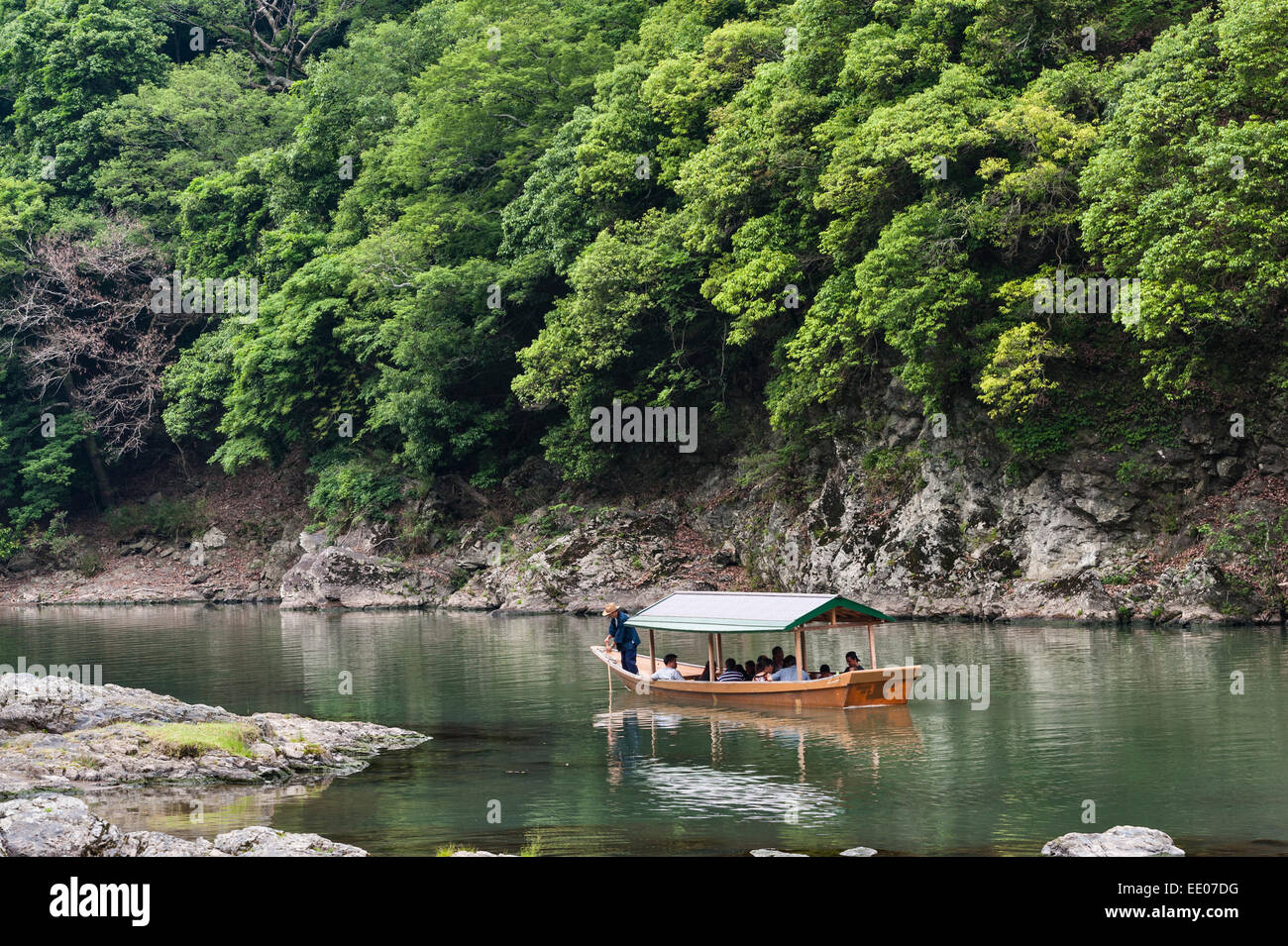 Arashiyama, Kyoto, Japan. Tourists taking a boat trip along the Katsura River - Stock Image