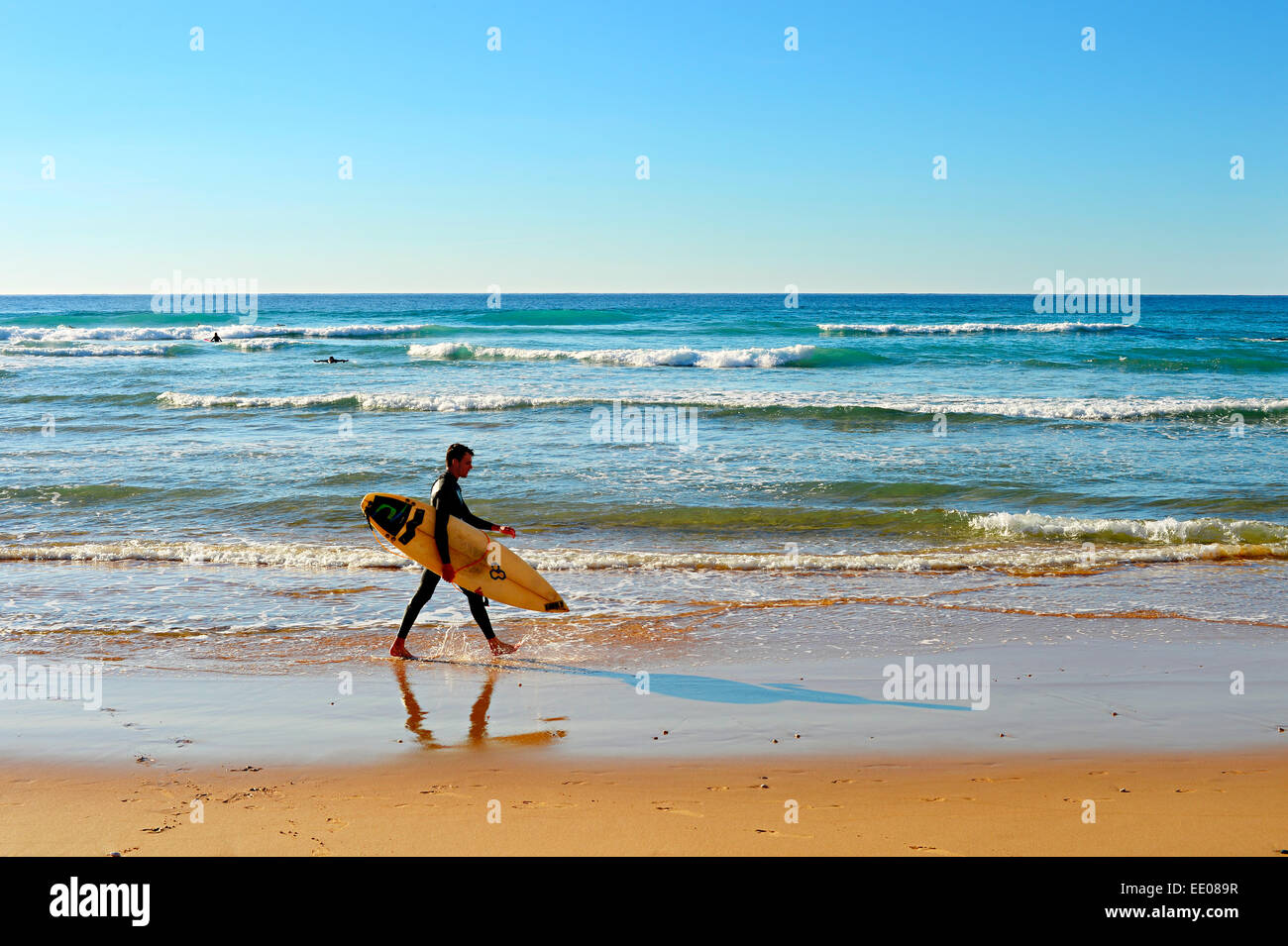 Unidentified surfer walking on the beach. Stock Photo