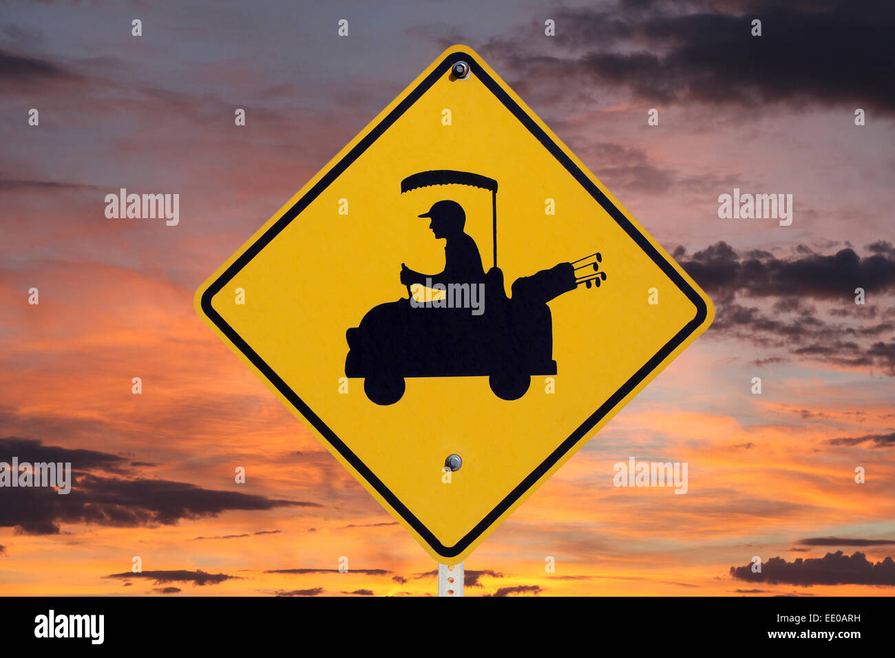 Golf cart crossing caution sign with orange sunrise. - Stock Image