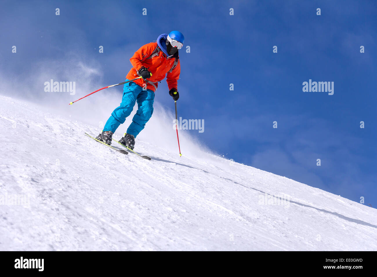 Skier skiing downhill in high mountains and sunny day - Stock Image