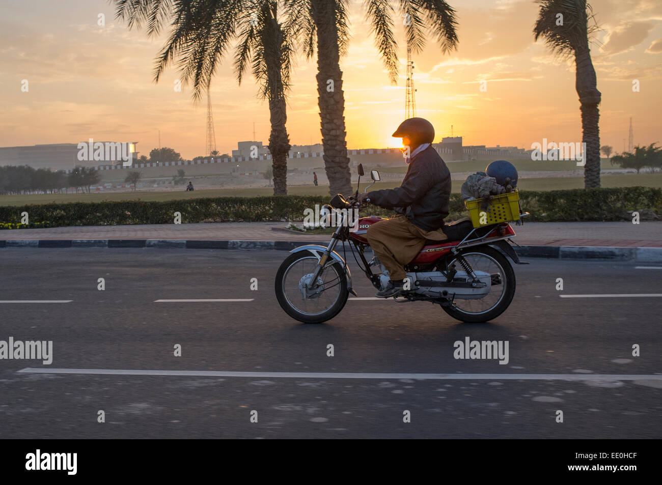 A migrant worker heads for work on a motorbike in Doha, Qatar at sunrise - Stock Image
