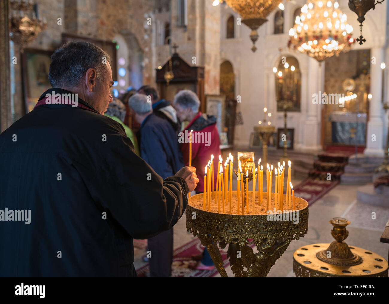 Man lighting a candle in a Greek Orthodox church. In the village of Exohori, Outer Man, Peloponnese, Greece. - Stock Image