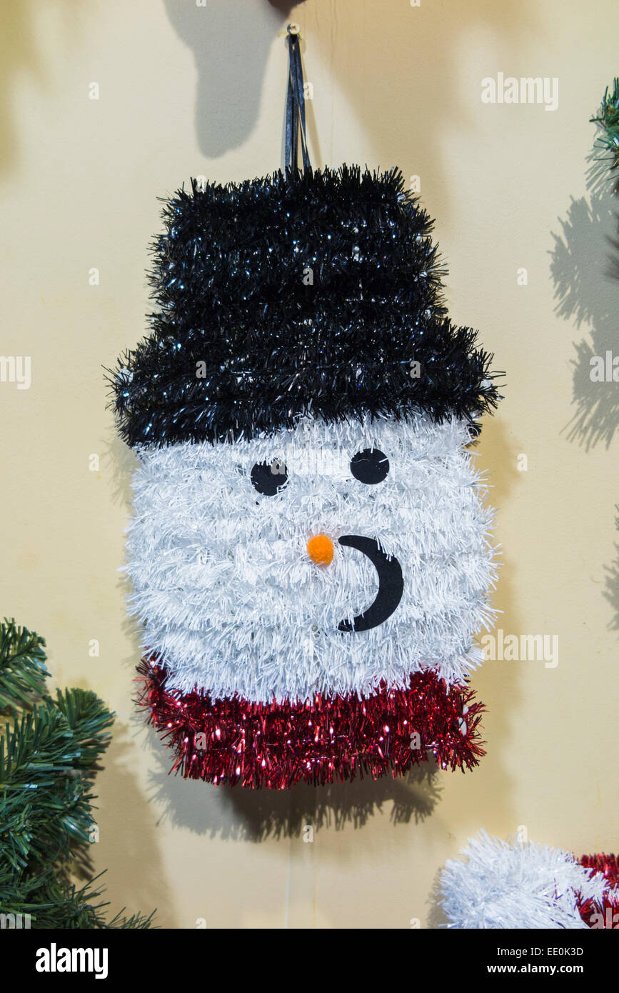 White snowman with black hat tinsel Christmas tree or wall decoration - Stock Image