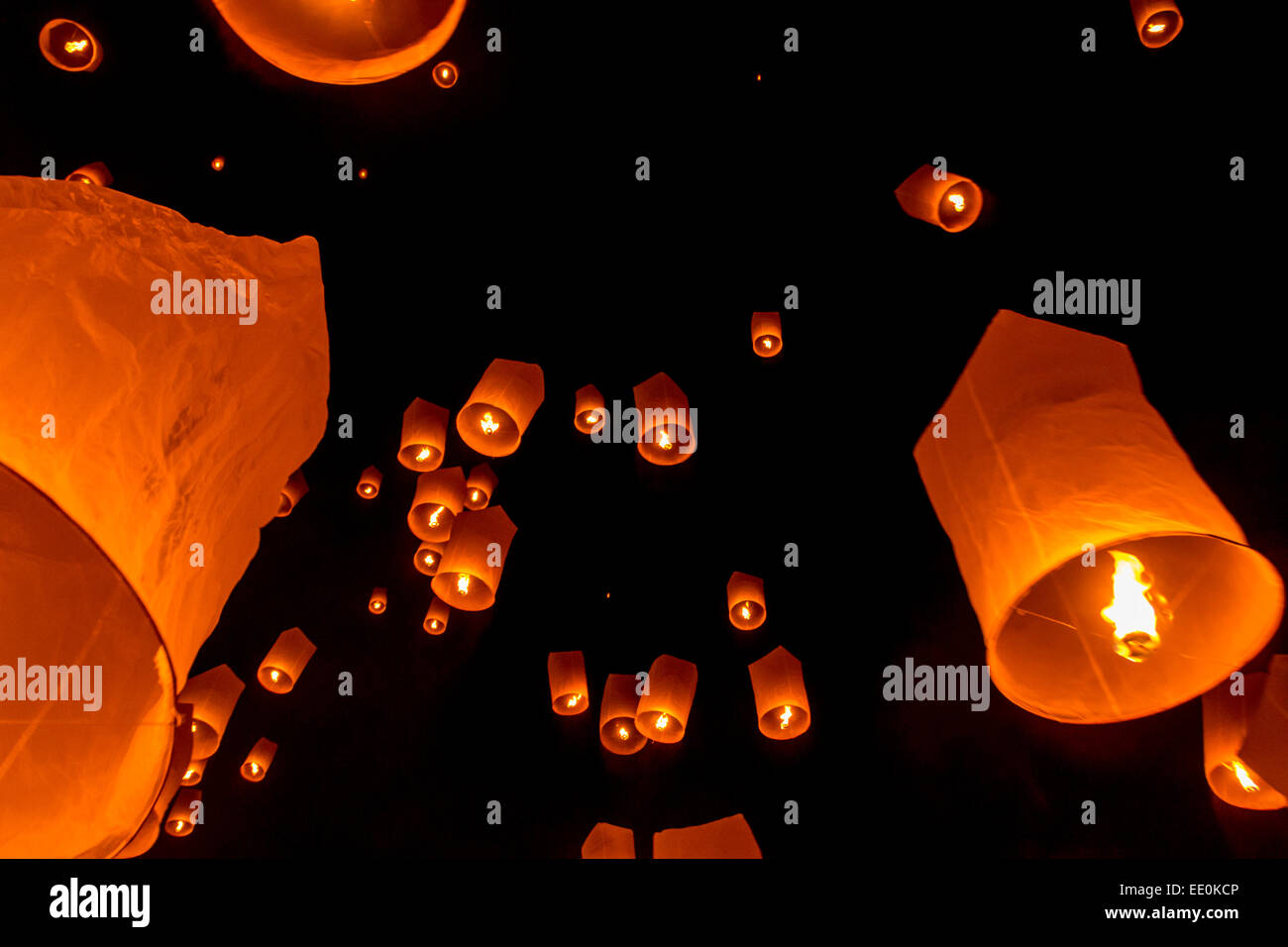 lighted paper lanterns float skyward into the dark night as part of
