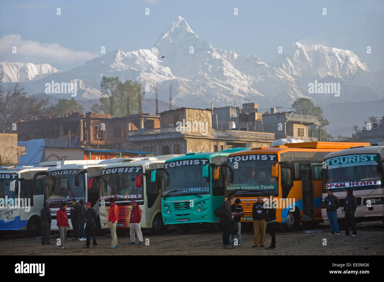 Tourist coaches and Himalayan peaks at Pokhara, Nepal. - Stock Image