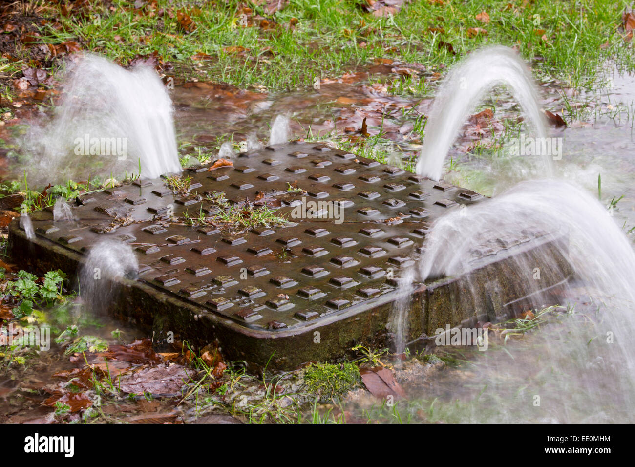 A man hole cover being pushed up under the force of water pressure during flooding in Ambleside, Lake District, - Stock Image