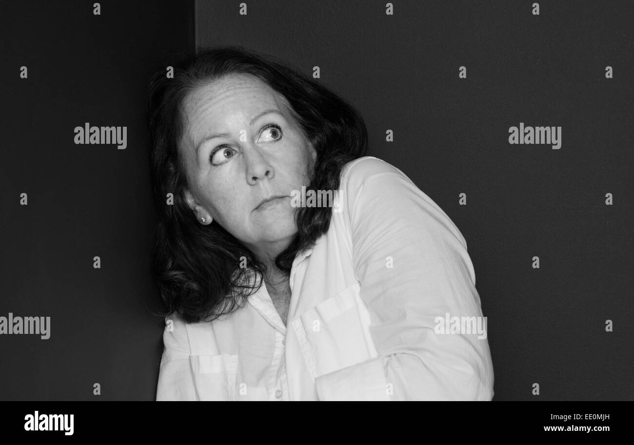 Woman in a corner with a look of paranoia in black and white - Stock Image