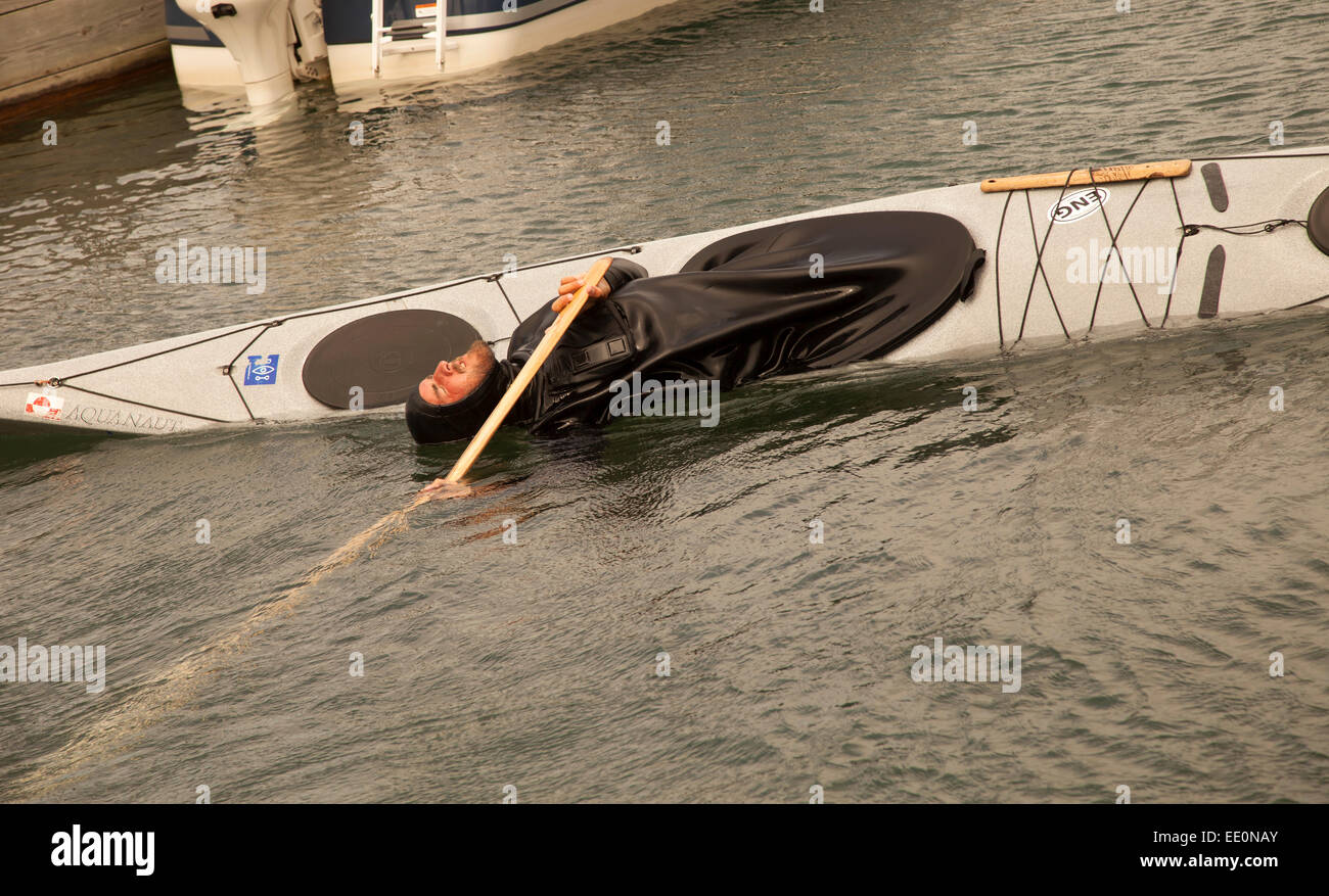 Man demonstrating how to turnover in a kayak. - Stock Image