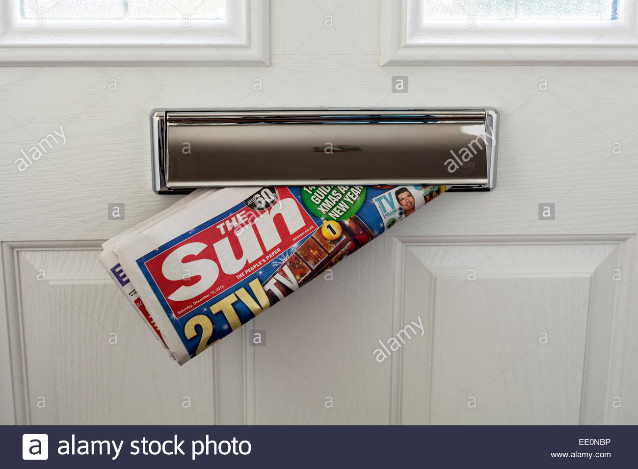 The Sun newspaper delivered through a letterbox - Stock Image