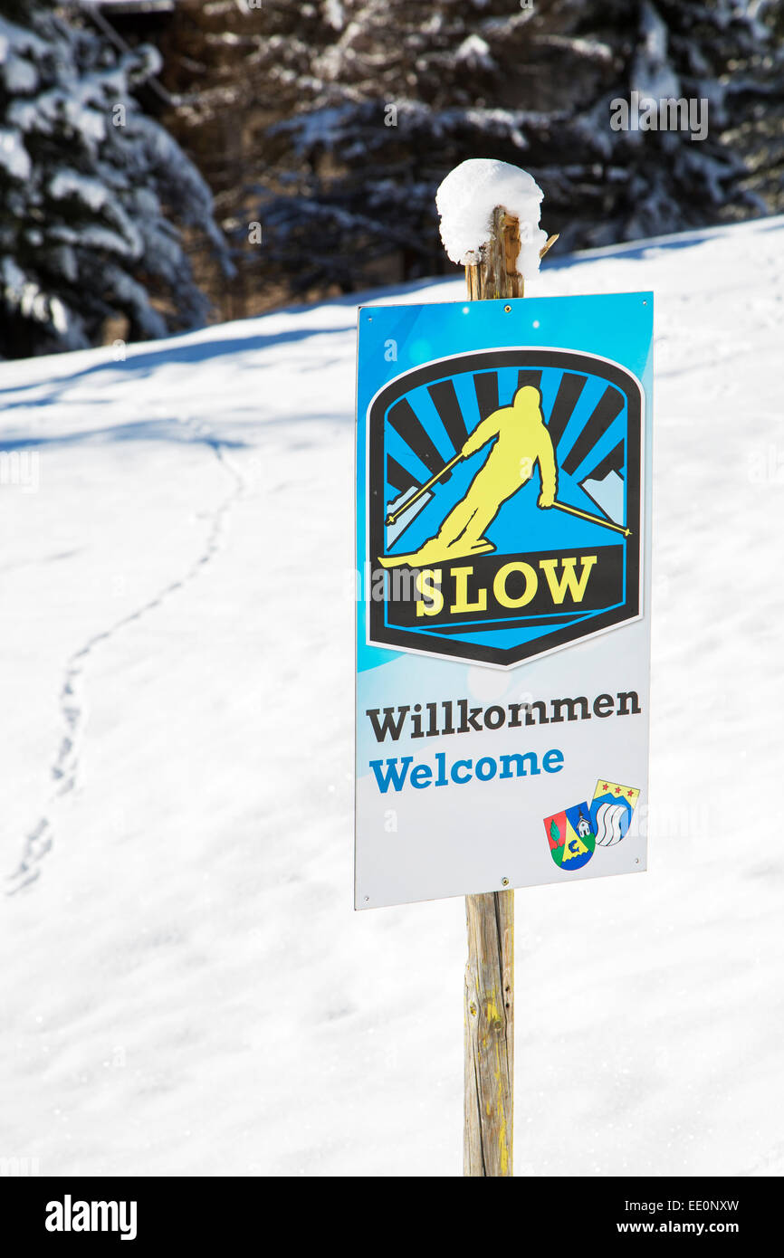 Welcome sign urging skiers to skiing slowly in Alpine ski station in the Swiss Alps in winter - Stock Image