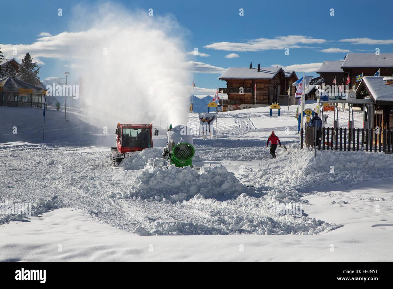 Snow cannon / snowgun and snow groomer vehicle preparing ski run in winter at Riederalp, Wallis / Valais, Switzerland - Stock Image