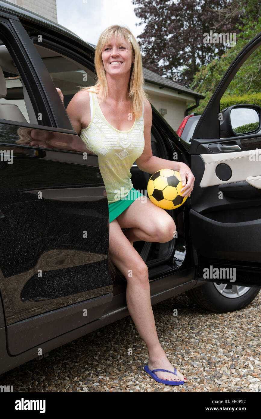Woman In Short Skirt Getting Out Of A Car Holding A