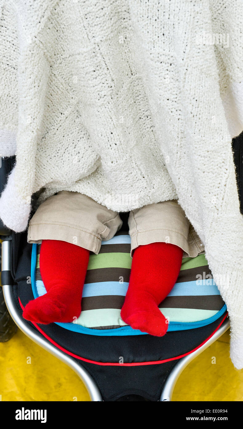 A baby asleep in a buggy under a blanket, with only its feet visible in a bright red babygro (babygrow) - Stock Image