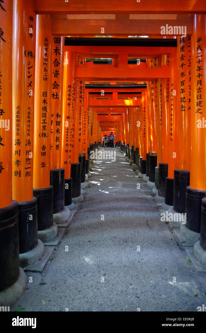 Red torii with donor's name at Fushimi Inari Shrine in Kyoto, Japan - Stock Image