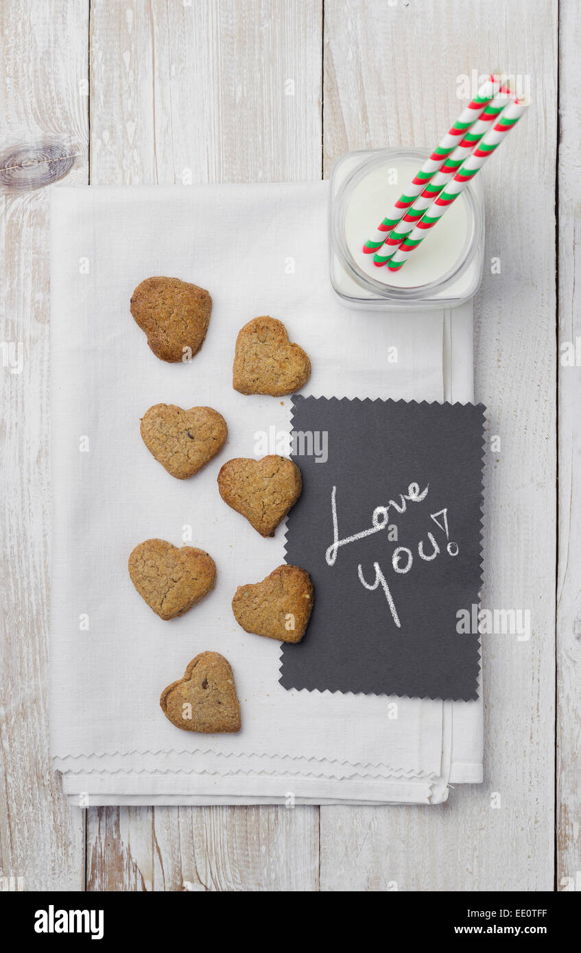 Heart shaped cookies, milk and 'Love you' handwritten card - Stock Image