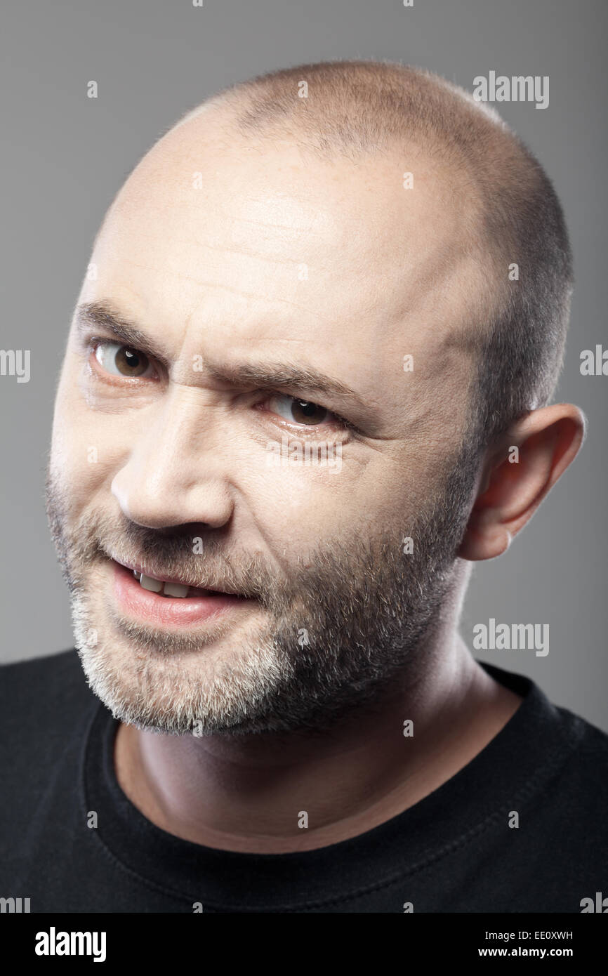 portrait of skeptical looking man isolated on gray background - Stock Image