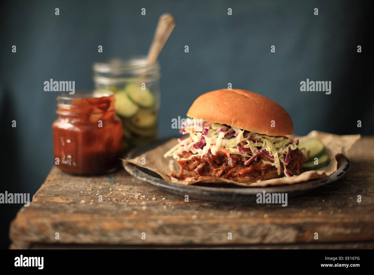 A Pulled Pork Sandwich served with Slaw and pickles. - Stock Image