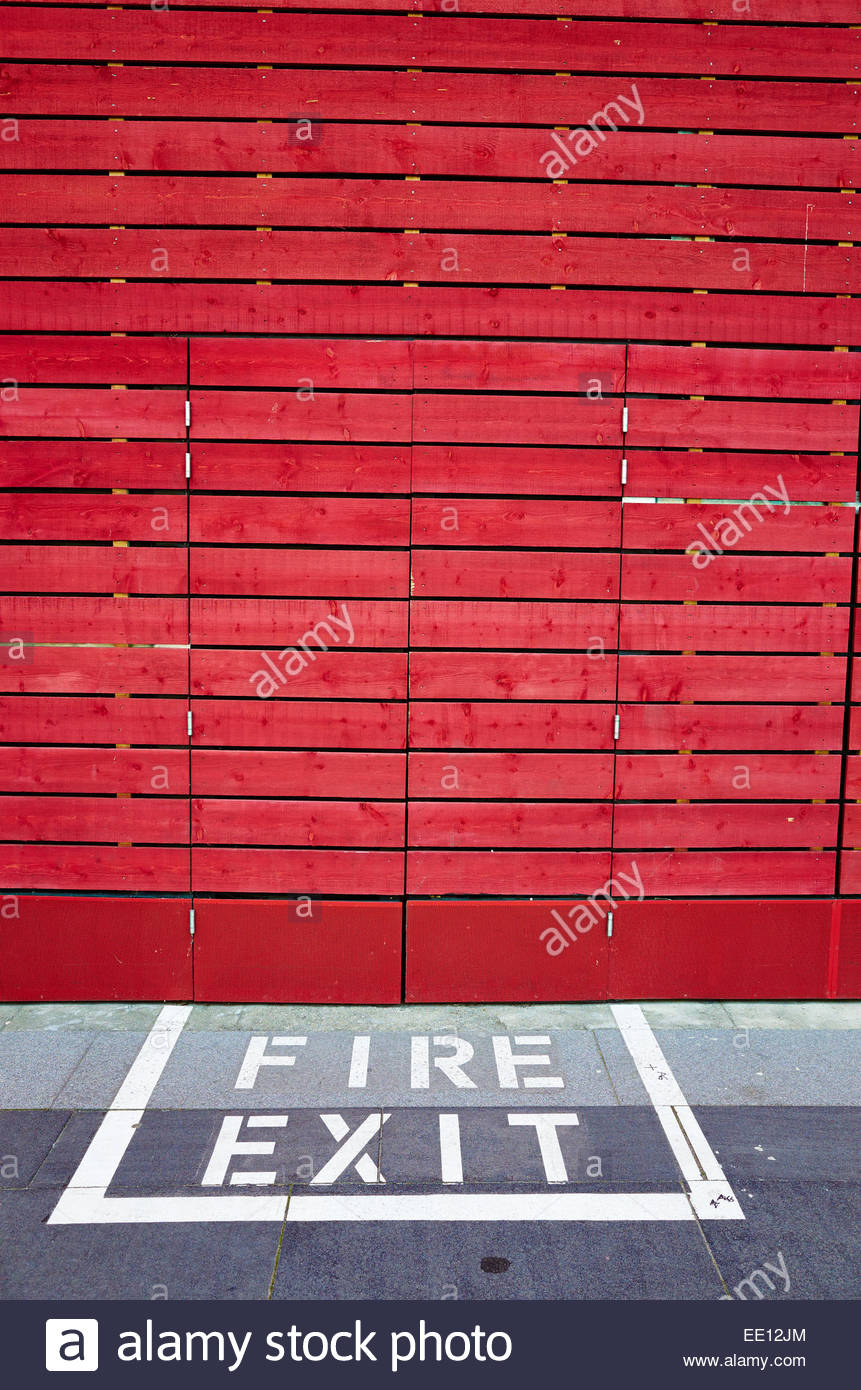 Red Wall with Fire Exit sign written in floor at the London Southbank Centre - Stock Image