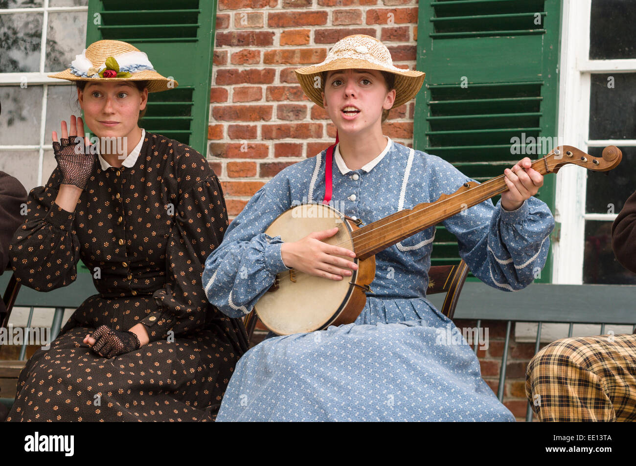 Musical Entertainment at Upper Canada Village. One woman listens for audience response while the other sings and - Stock Image