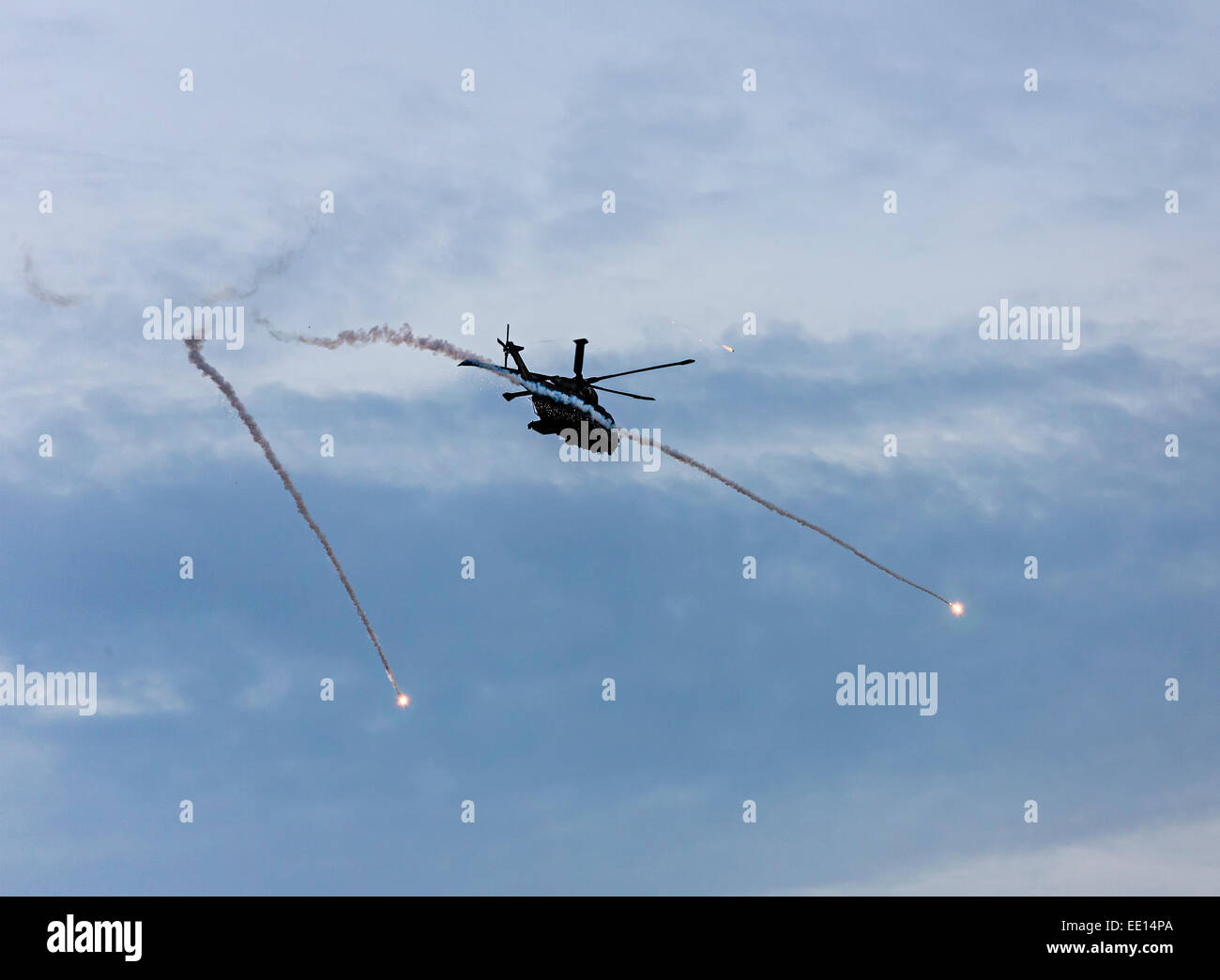 Military helicopter firing flares during training exercise, Donna Nook, Lincolnshire, England, UK - Stock Image