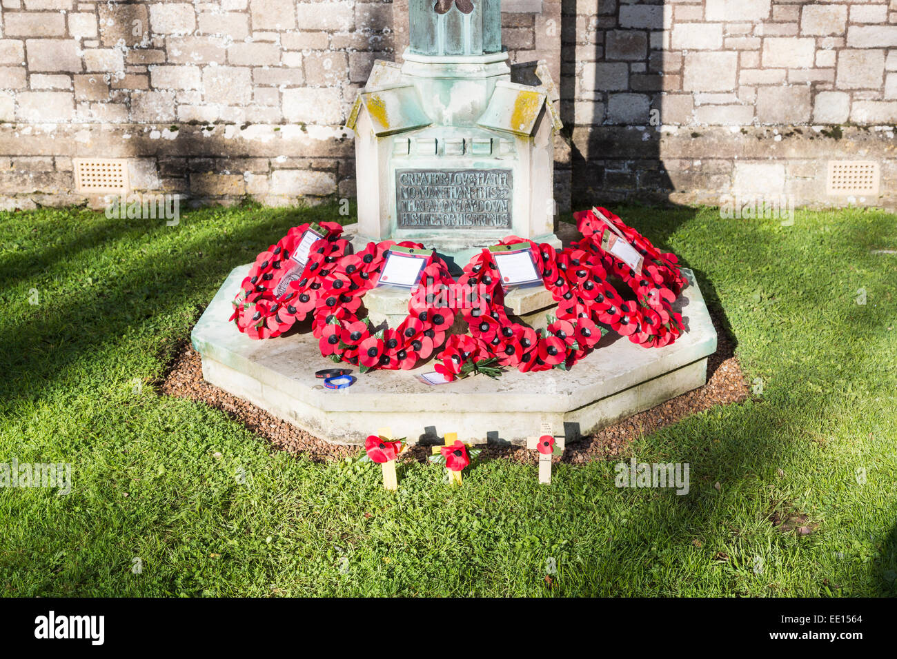 Poppy wreaths for Remembrance Day on the war memorial at St Mildred's Church, Whippingham, Isle of Wight, Hampshire, - Stock Image