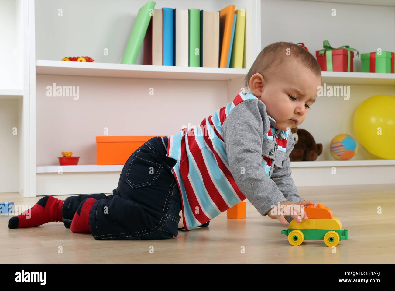 Portrait of a baby playing with car toy in children's room Stock Photo