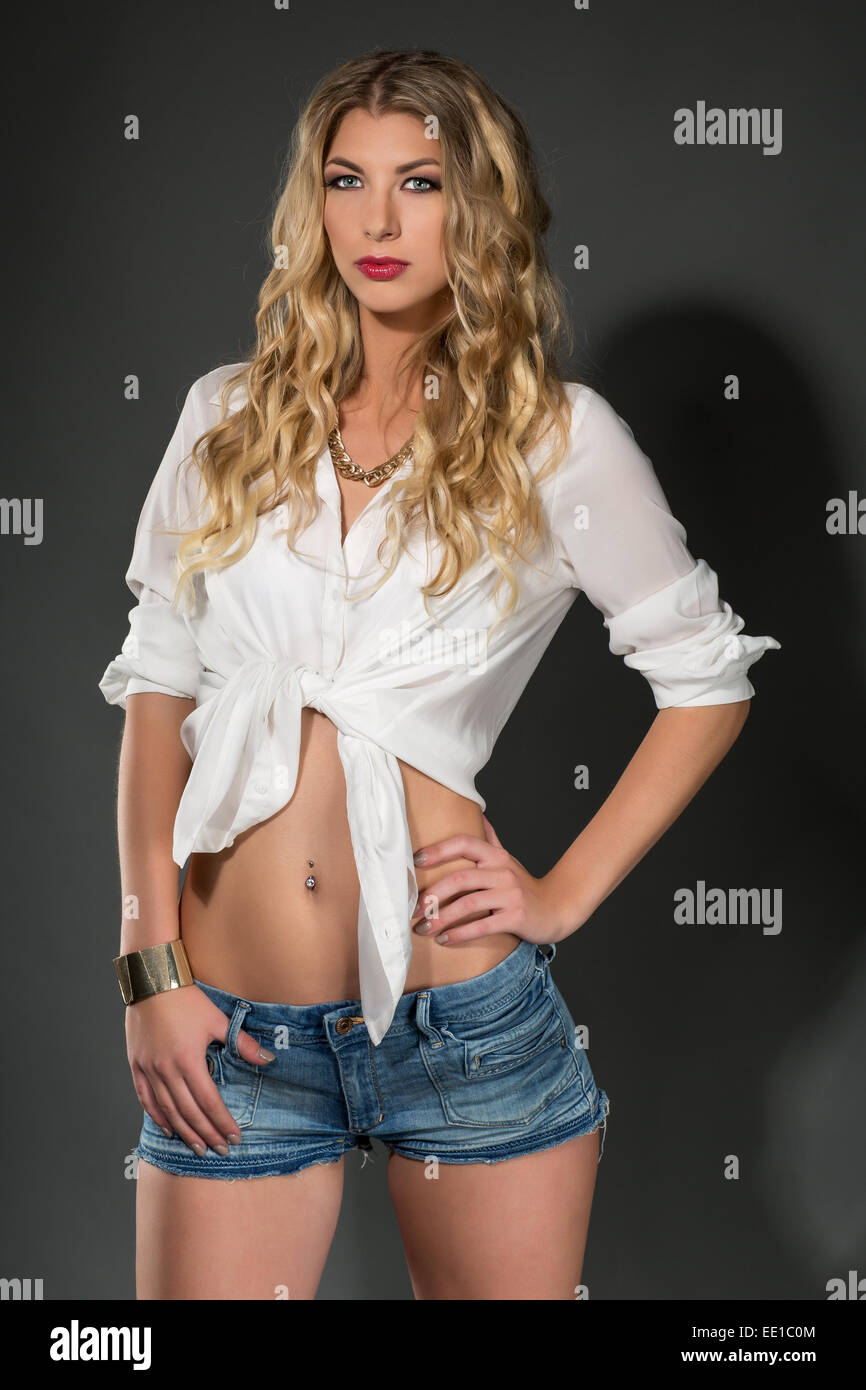 1a651e8e282b6 Young woman wearing a white shirt and blue jeans hot pants - Stock Image