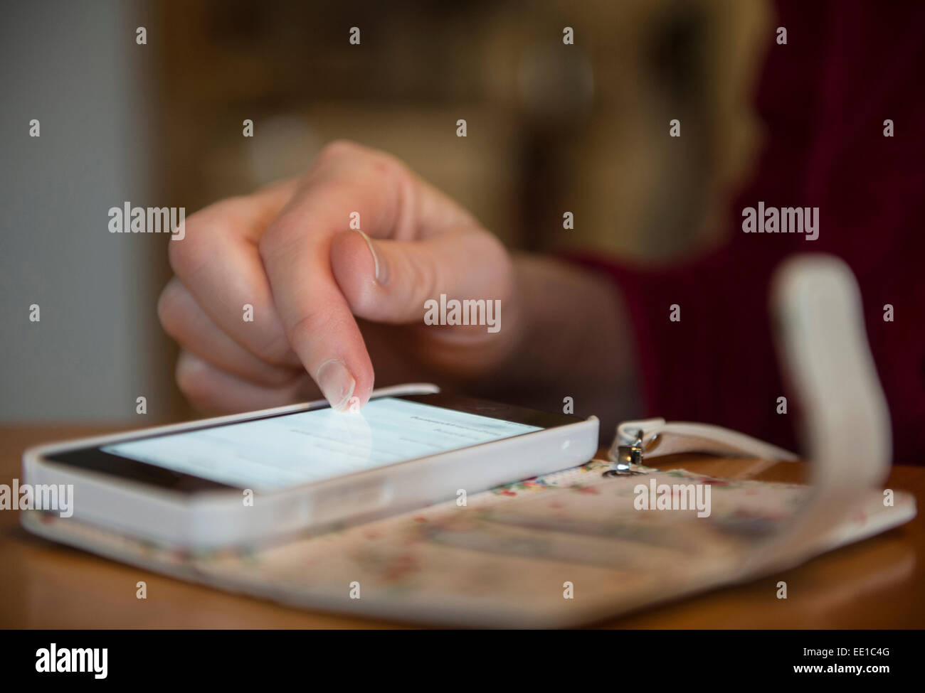 Female texting on a white smartphone i phonecase - Stock Image
