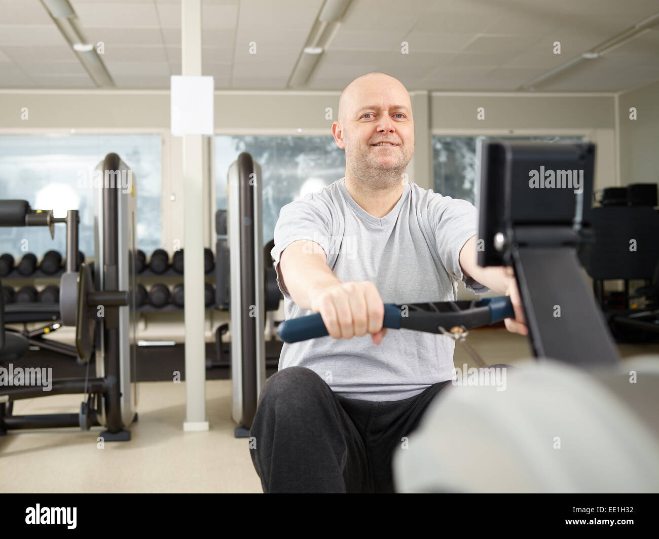 Mature man takes care of his health and he rowing in the gym - Stock Image