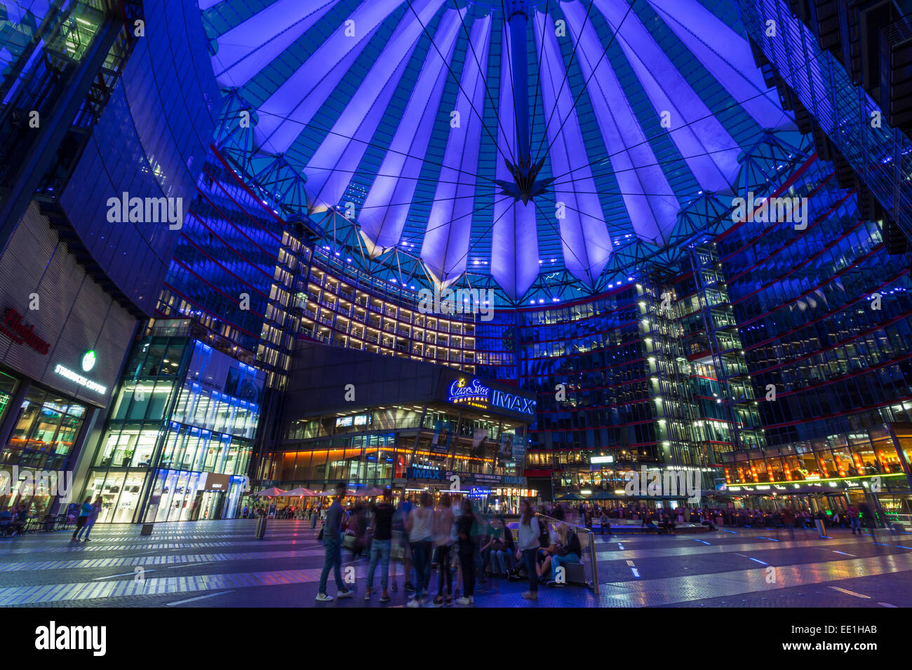 Young people relax and socialise in an illuminated Sony Center at night, Potsdamer Platz, Berlin, Germany, Europe - Stock Image