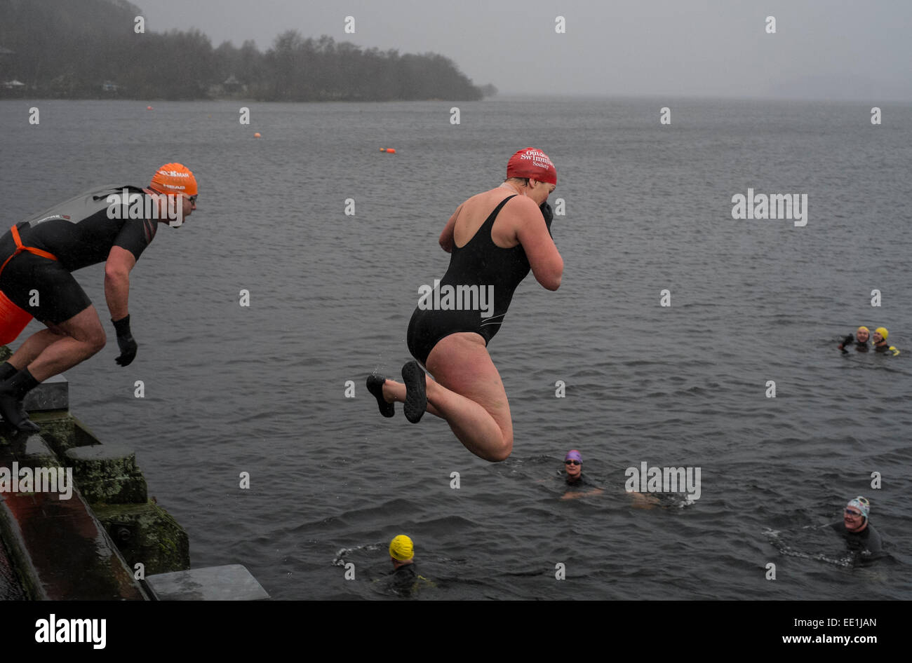 New Years Day swimmers take to the water from the pier at Luss in to the freezing waters of Loch Lomond, Scotland. - Stock Image