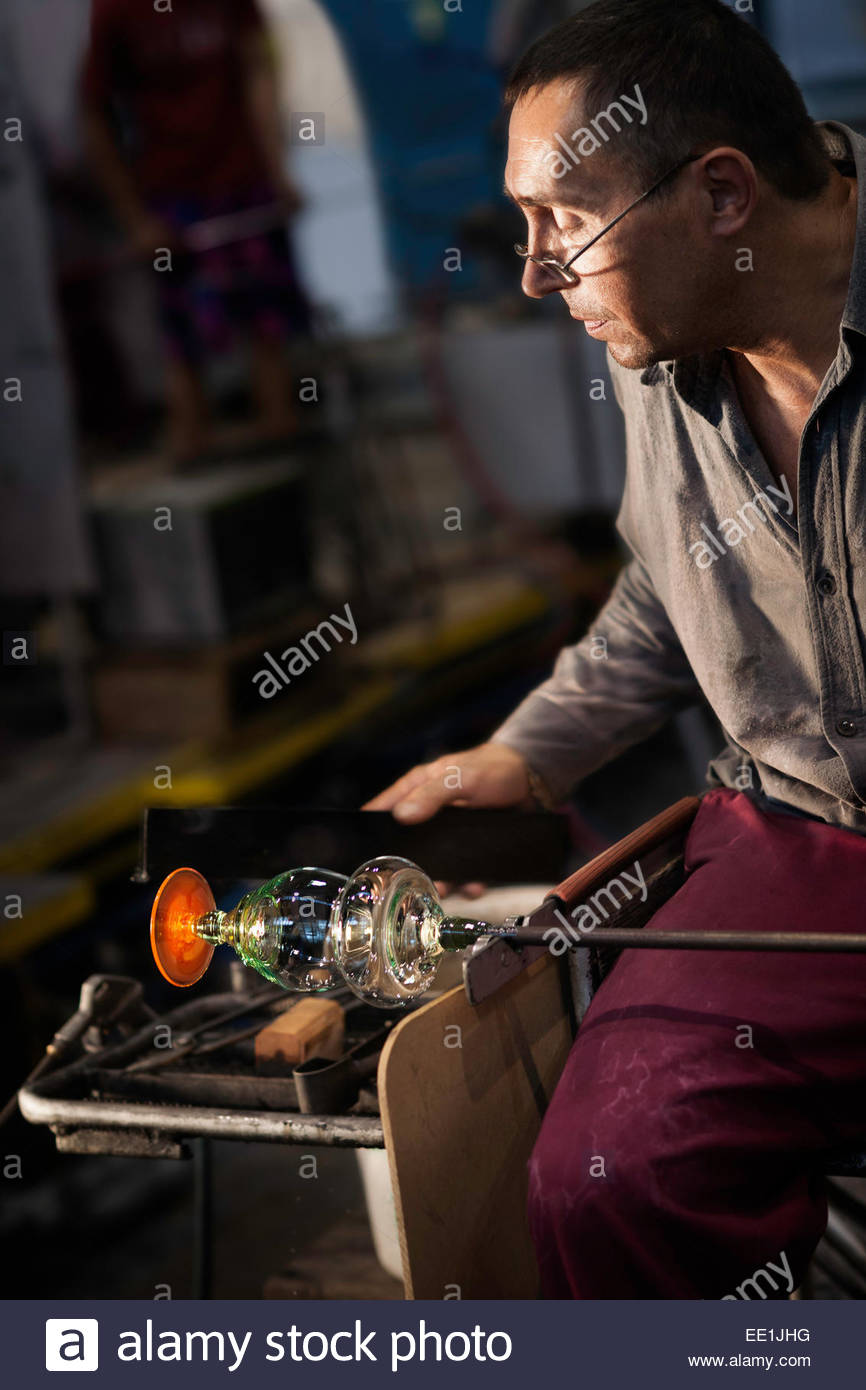 Male glass blower at Moser Glass Factory in various stages of crafting crystal goblets, Karlovy Vary (Karlsbad), - Stock Image