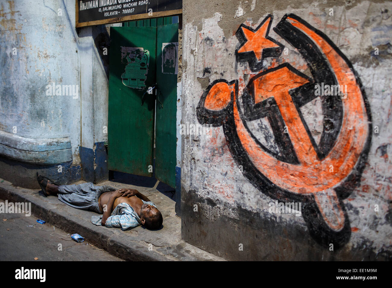 A person sleeps under a Communist Party symbol in dark alley of Kolkata, India - Stock Image