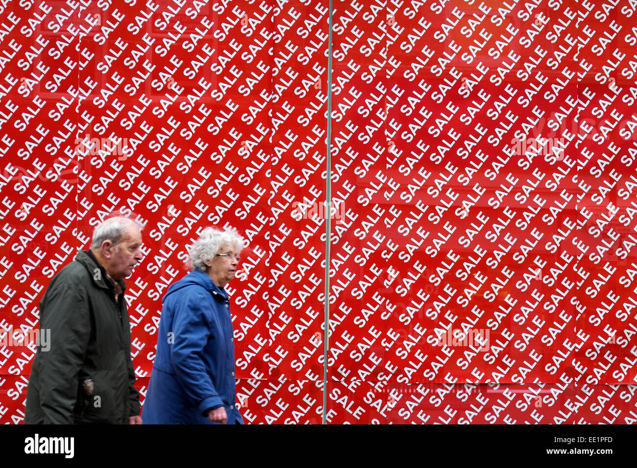 Shoppers walking past a huge sale sign in a shop window. - Stock Image