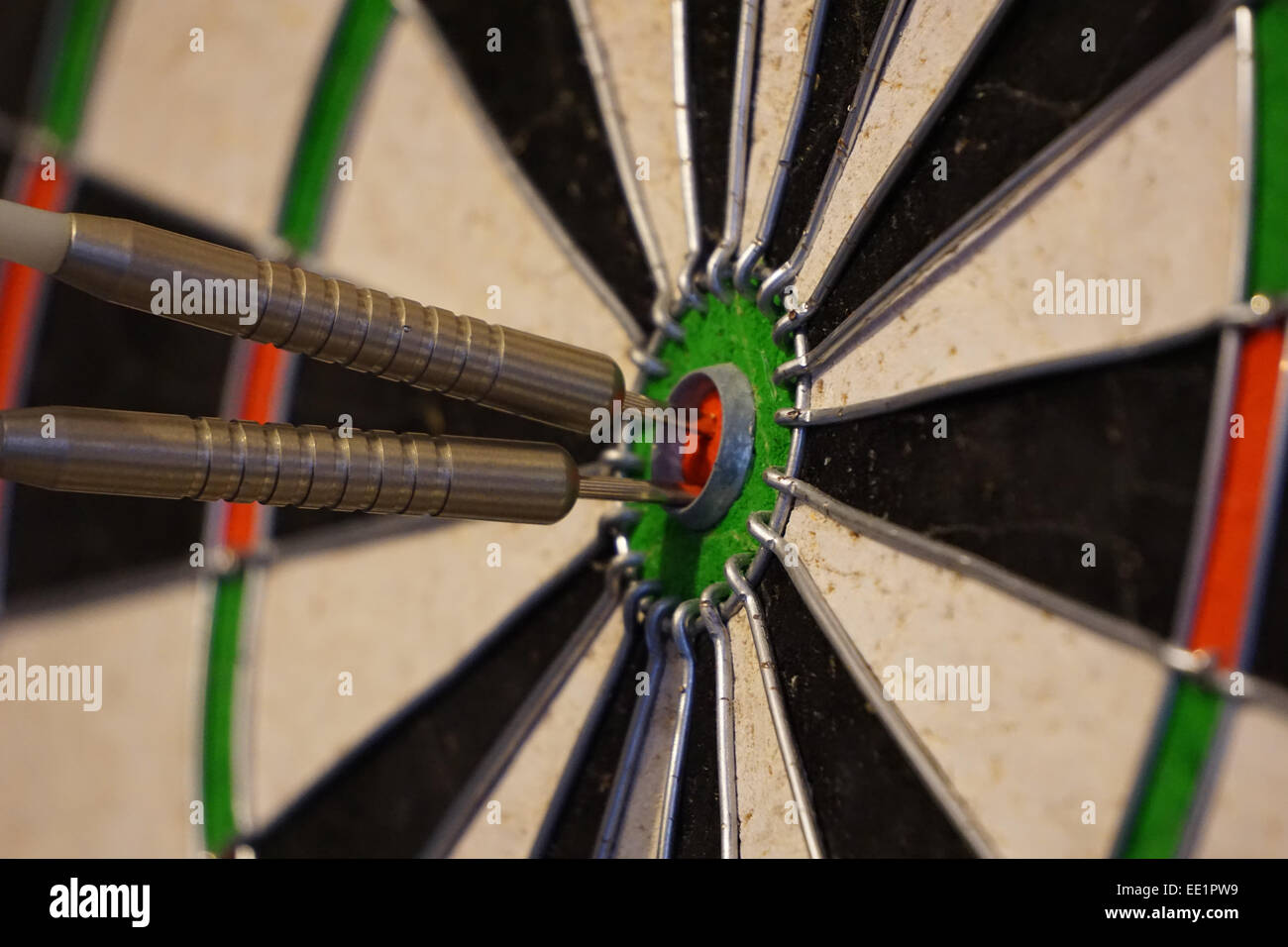 Two darts in the bulls eye of a dart board. - Stock Image