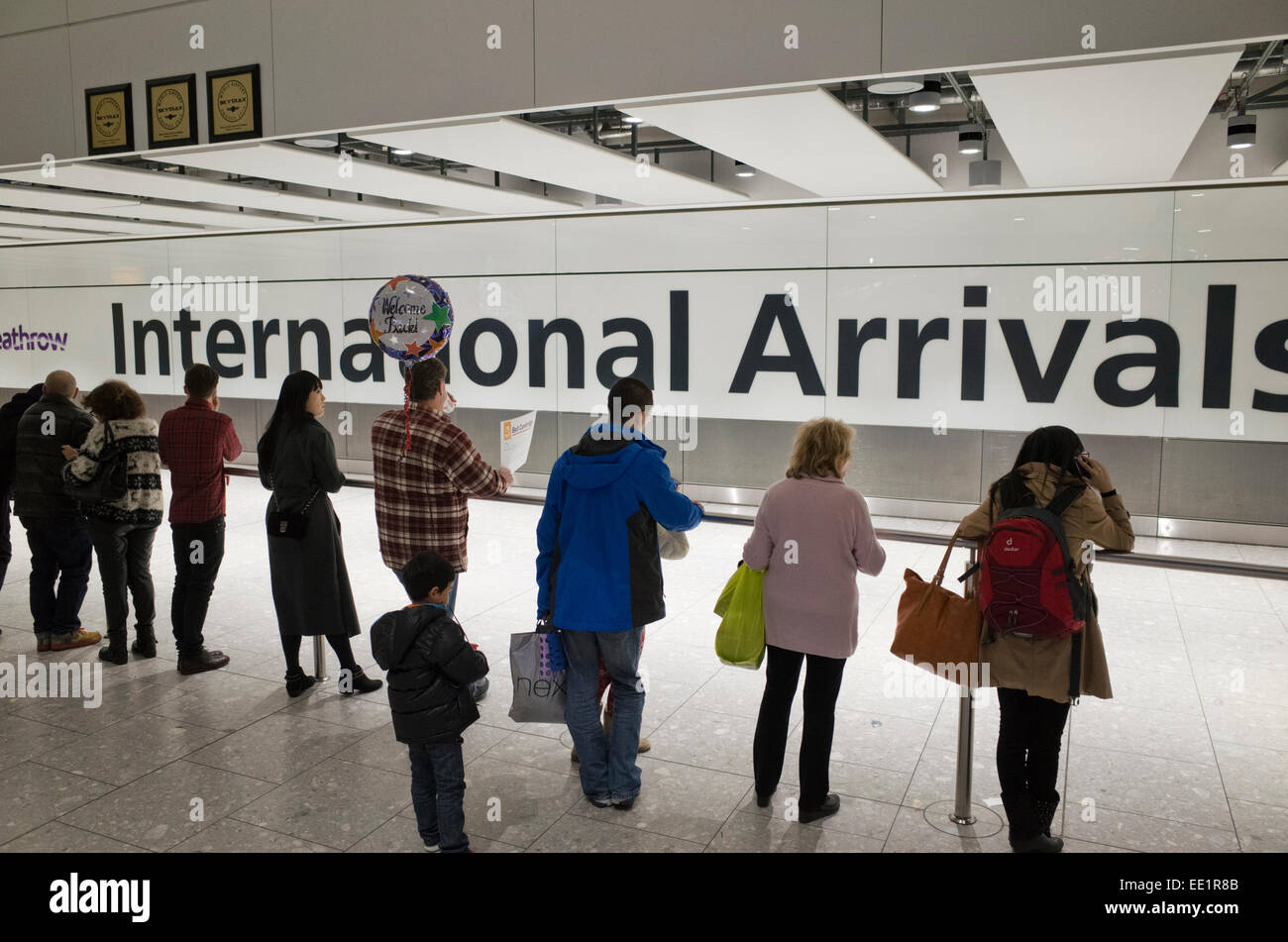 People waiting at International Arrivals at Heathrow airport in Britain - Stock Image