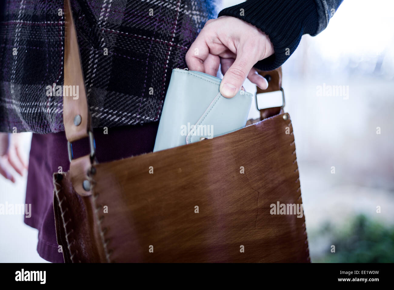 Pickpocket Stealing a Wallet from a Leather Bag - Stock Image
