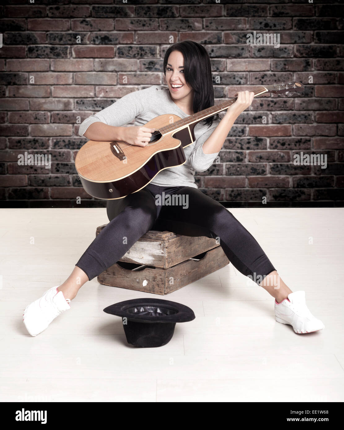 Young female busker sitting on a wooden box playing her guitar for money. - Stock Image