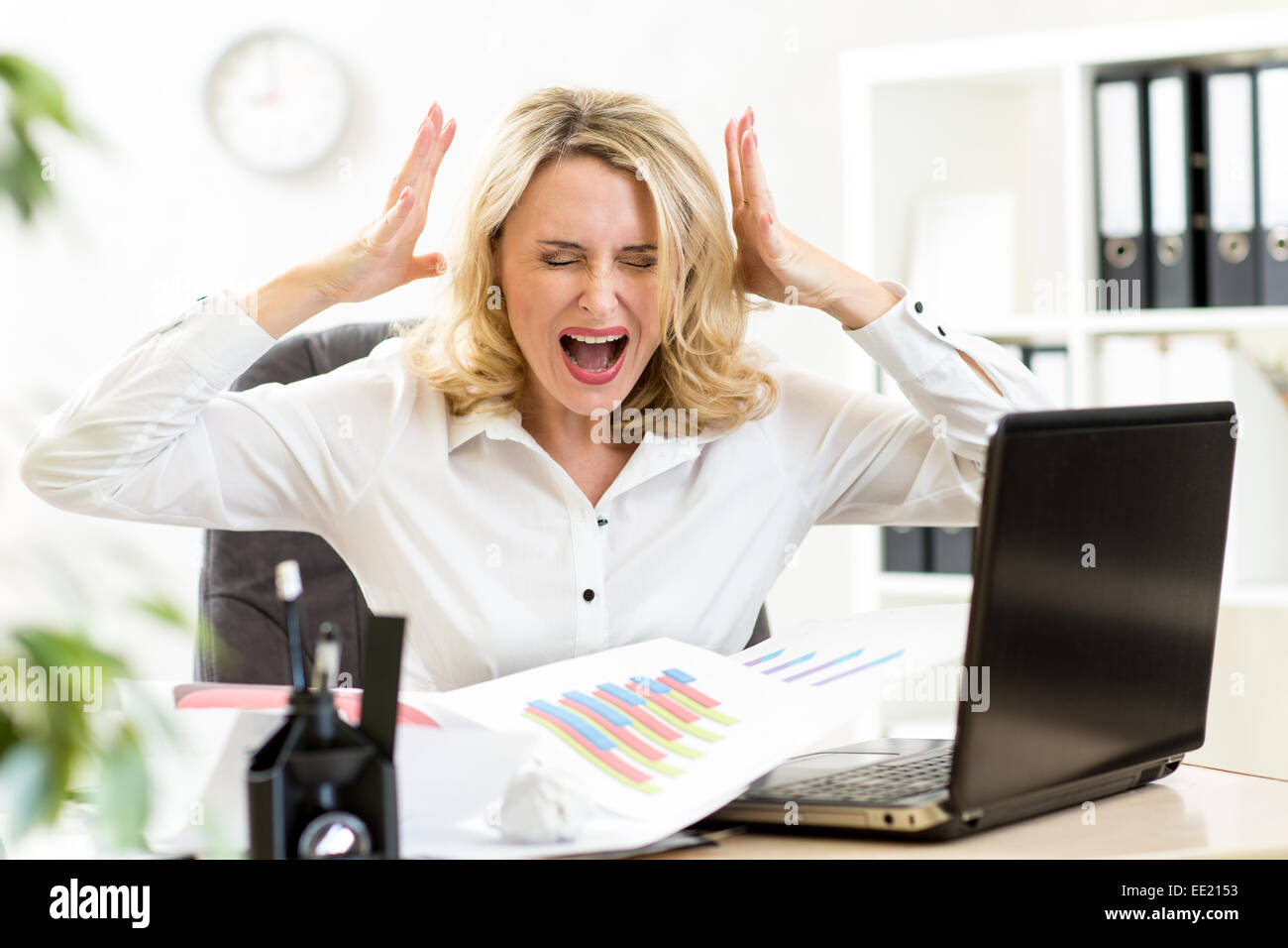 Stressed business woman screaming loudly working in office - Stock Image