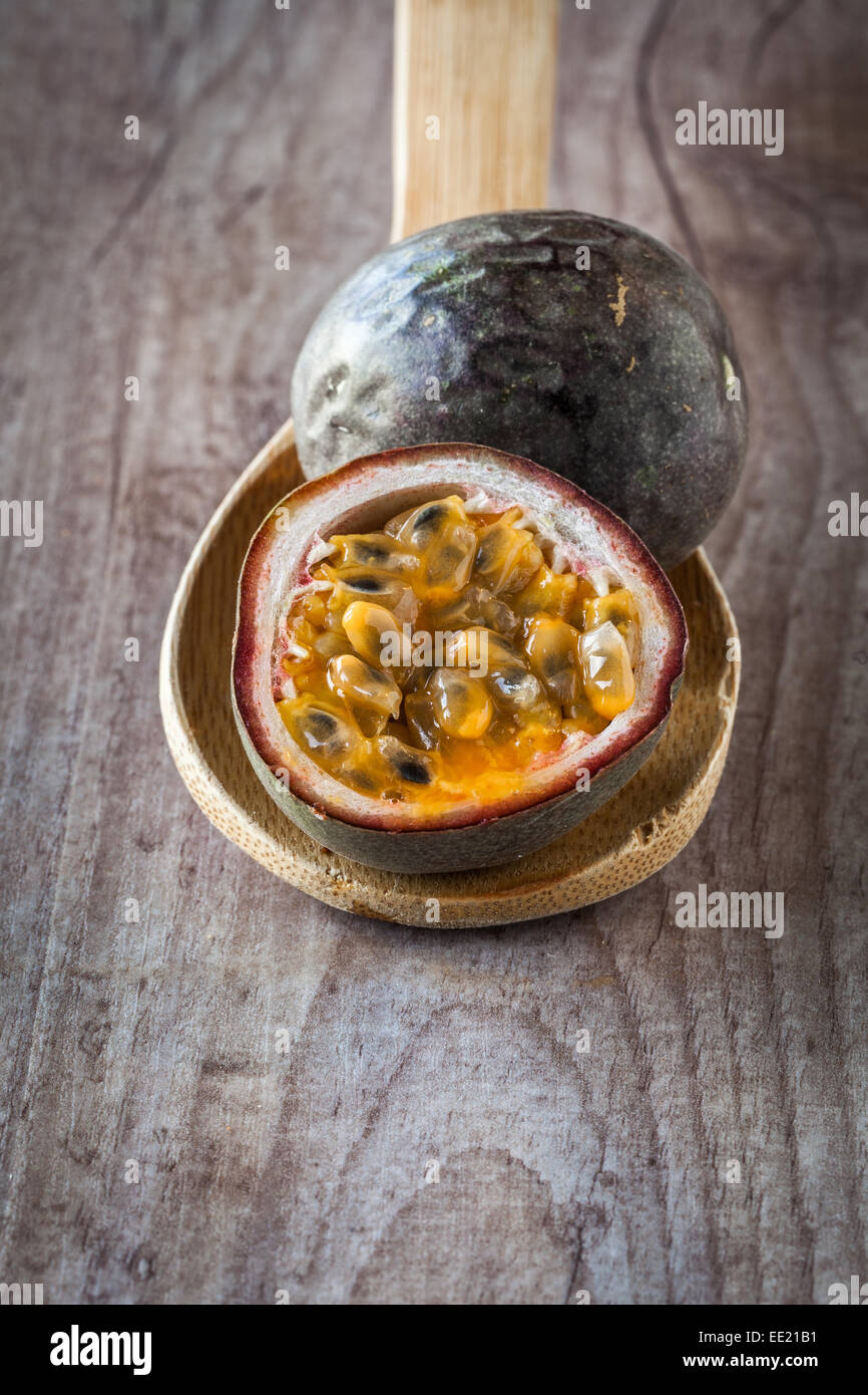 Fresh juicy passion fruit on wooden background - Stock Image