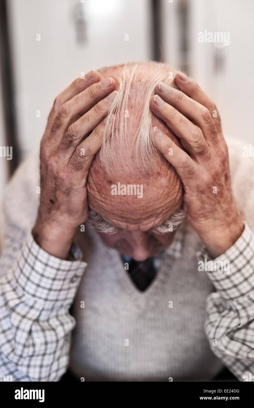 Holding ones head deep in though worrying and contemplating the sadness and happiness of previous times memories Stock Photo