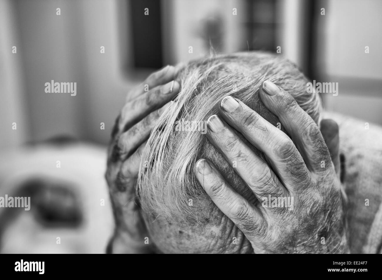 Holding ones head deep in though worrying and contemplating the sadness and happiness of previous times memories - Stock Image