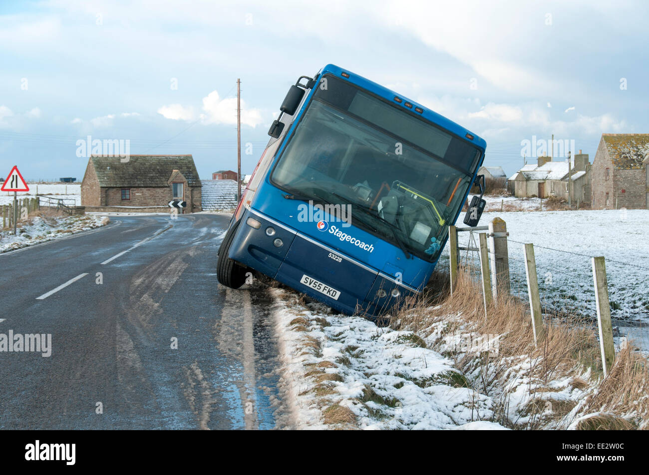 A bus skidded into a ditch after an overnight snowfall and freezing temperatures led to icy conditions on the road. - Stock Image