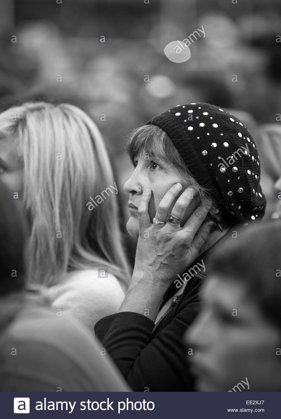 Woman in a crowd, visibly moved (touched) - Stock Image