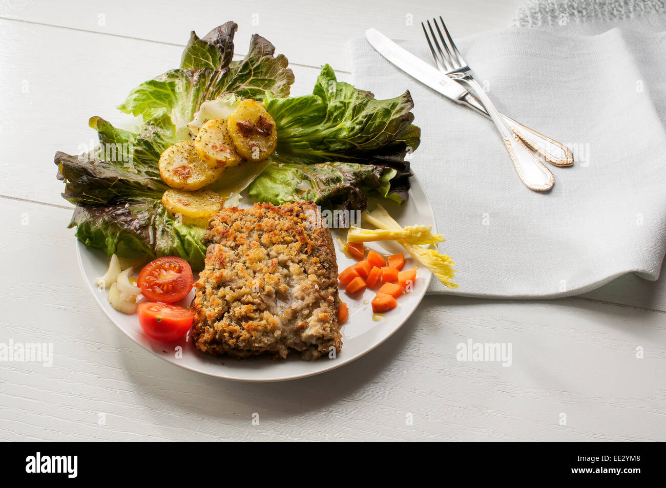 cod fillet breaded and baked with potatoes and salad as garnishing - Stock Image