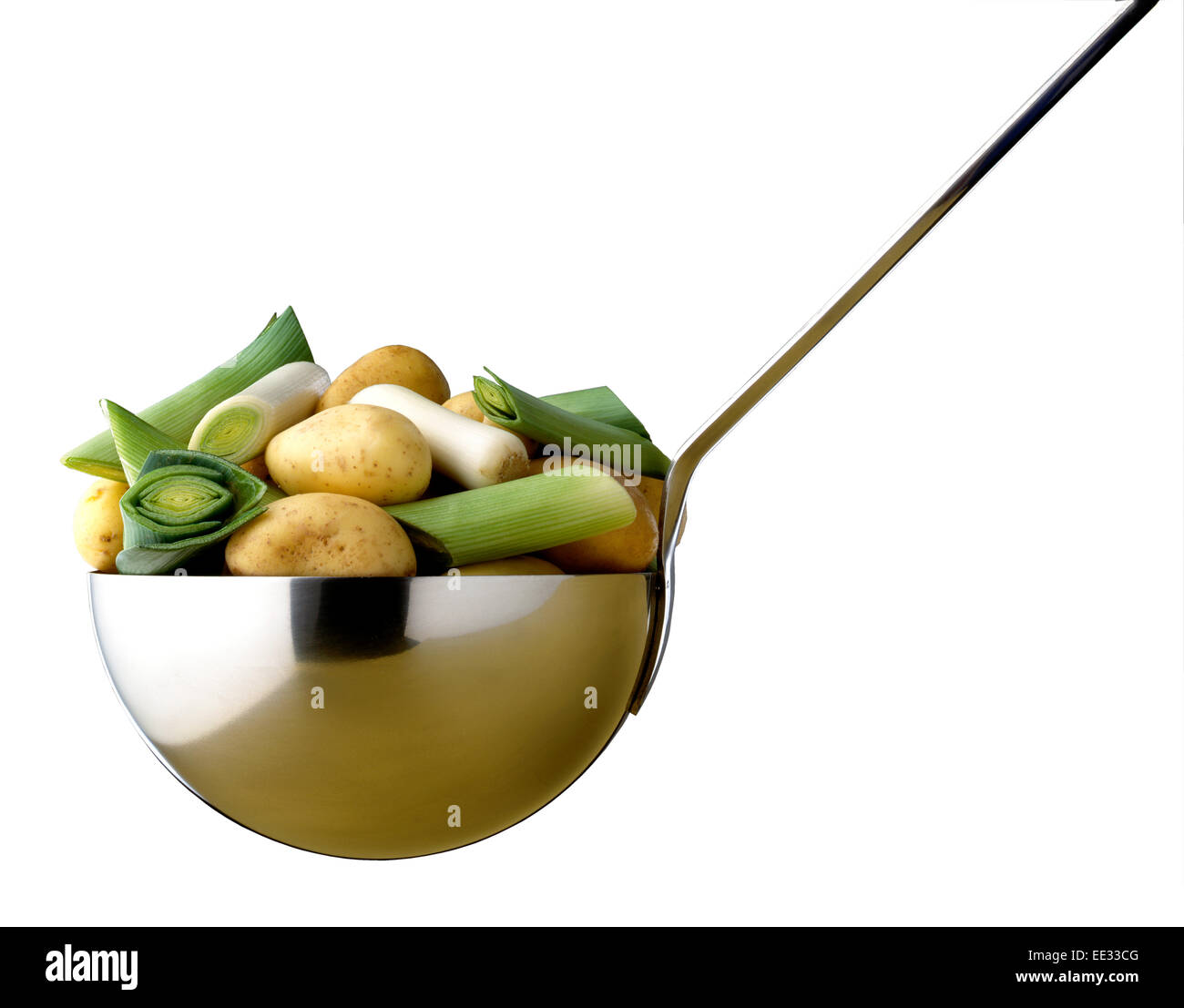 leek and potato soup ingredients in large ladle - Stock Image